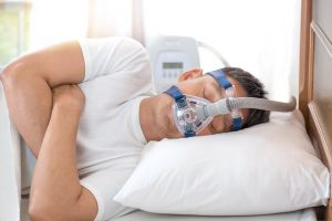 showing a man sleeping with a cpap mask laying on the side
