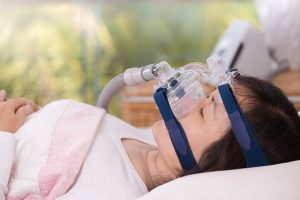 showing a woman wearing a cpap mask laying on her back