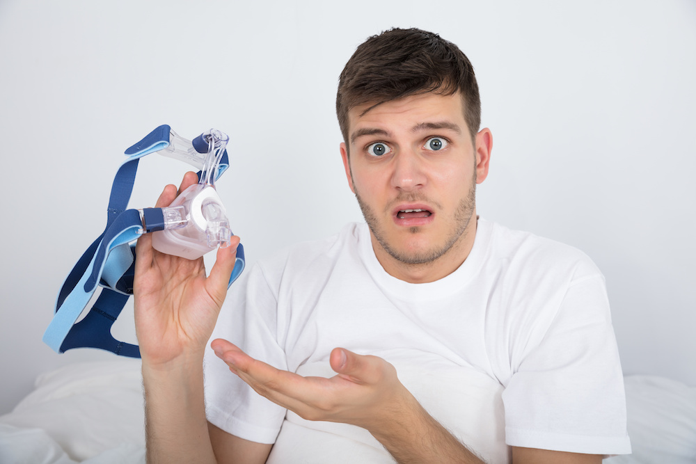 Young Man Holding CPAP mask